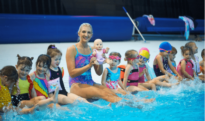 Lily on side of pool with Rebecca Adlington and Baby Annabell Learns to Swim Doll